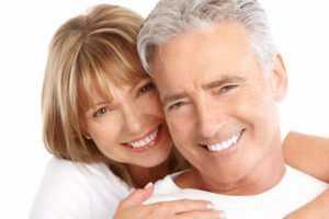 Happy couple smiling with perfect smiles from dentures and implant therapy in Port St. Lucie.