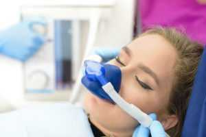Woman with mask over face from sedation before seeing the oral surgeon.